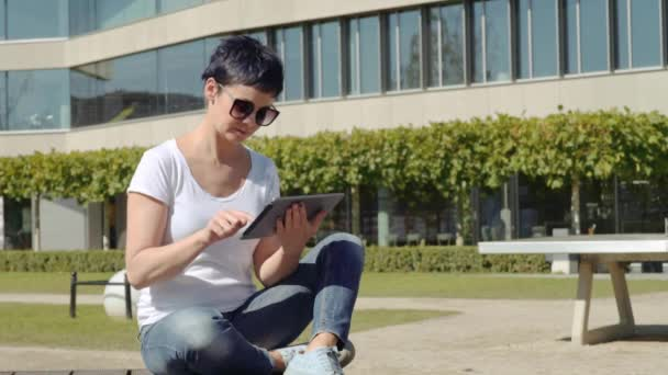 woman in a white T-shirt sitting in front of an office building and working on a tablet