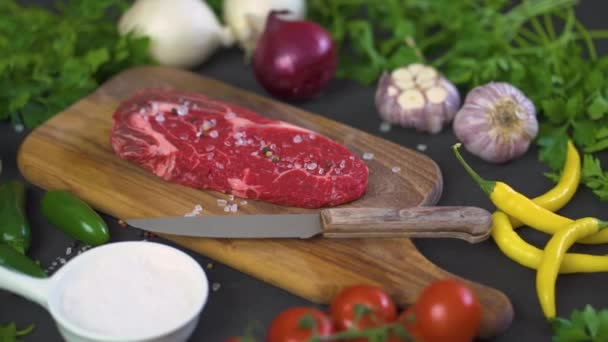 one raw piece of tasty steak with salt, pepper on a wooden board and a set of vegetables on a black table