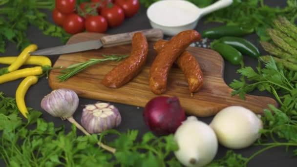 tři vynikající klobásy s jinou zeleninou na dřevěném prkénku, nůž na černý stůl