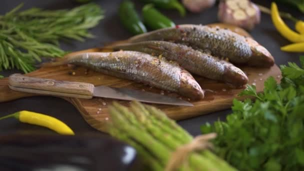 three fresh raw dorada fish on a wooden board with a set of vegetables on a black table