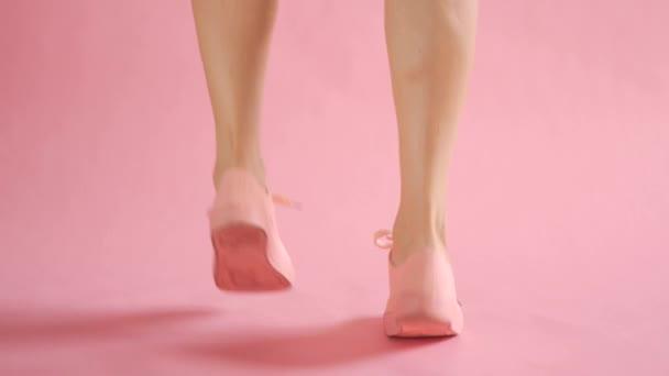 Blízkka štíhlých ženských nohou tančících v teniskách na korálovém pozadí