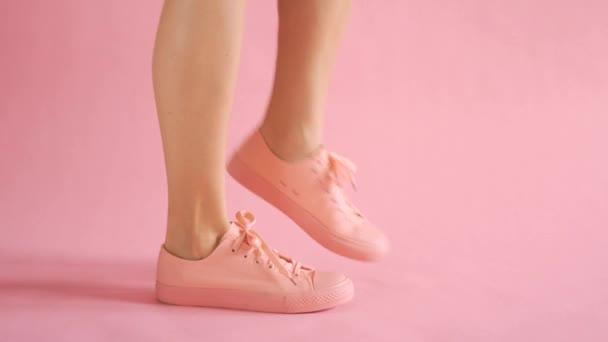 Nahaufnahme schlanker weiblicher Beine, die in Turnschuhen auf korallenfarbenem Hintergrund tanzen
