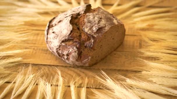 Sötét házi kenyér napraforgómag és rozs fülek a fából készült asztal