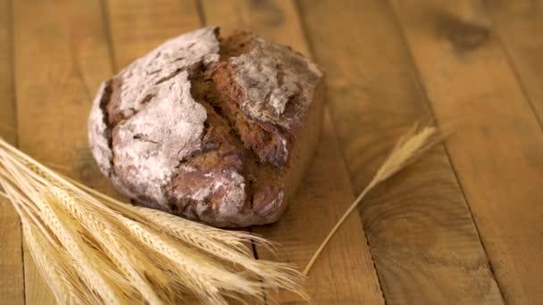 Tmavý domácí chléb s slunečnicovým osivem a žitným ušima na dřevěném stole