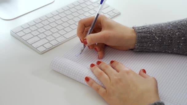 Poznámka: zápis ženských rukou v zápisníku vedle bílé počítačová klávesnice
