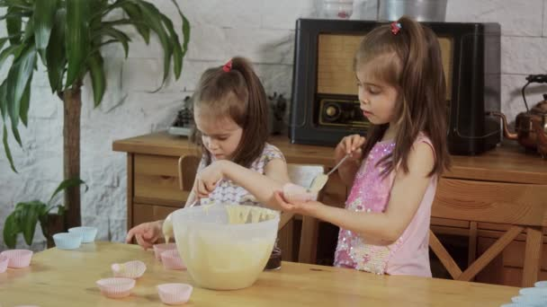 two little girls put cream on the molds to make cupcakes