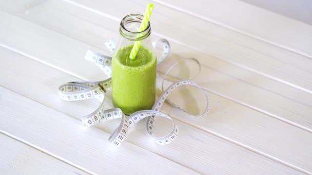 zdravý zelený a veganový koktejl s centimetru na bílém dřevěném stole
