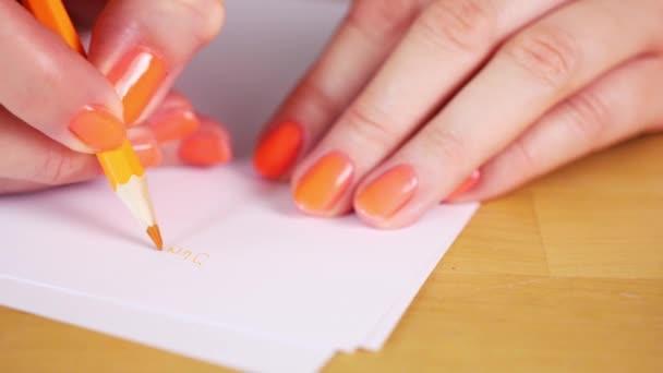 nő van kezében egy narancssárga ceruza és jegyzetel egy fehér papírt