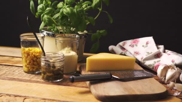 Cheese on chopping board and grater with fresh basil on wooden kitchen table