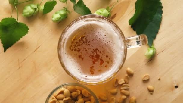Nejlepší pohled na pivo s pěnou a slanými oříšky a na dřevěném stole