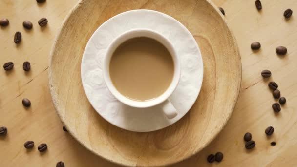 Pohled na šálek s aromatickou kávou s mlékem na dřevěném stole