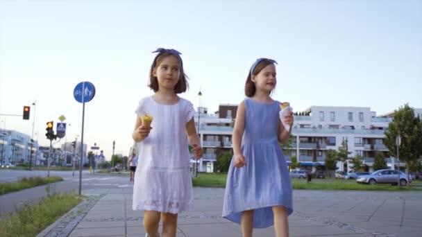zwei süße kleine Mädchen spazieren durch die Stadt und essen Eis