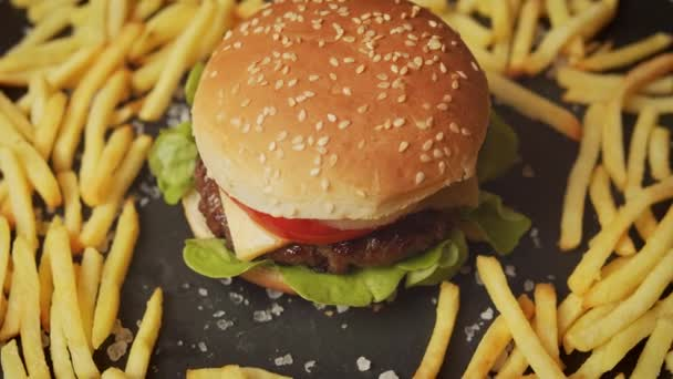 vynikající cheeseburger obklopený hranolky na černém stole