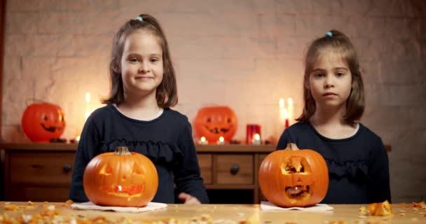 Két aranyos kislány egy tököt vág az asztalra Halloweenkor.