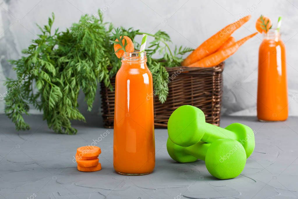 Two bottles with fresh carrot juice, green dumbbells and bunch of carrot in wooden basket on grey concrete background. Horizontal orientation, close-up, focus on one bottle and dumbbells.