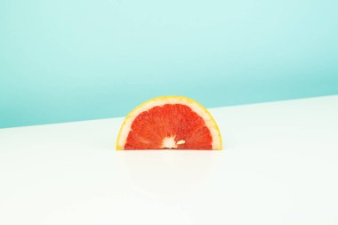 Piece of grapefruit on white and blue background. Minimalistic image of slice of citrus at sparse bright environment.
