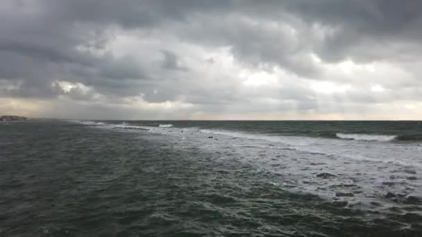 Dramatic weather over the sea threatening waves crashing at the shore with overcast sky and sunbeams on the water