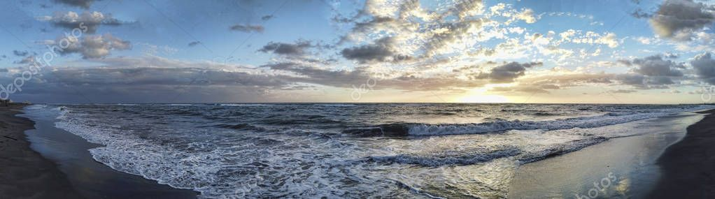 Scenic panoramic sunset at the sea in golden hour with awe cloudy sky , rough foam sea in a cold winter day in the Roman coast - Rome , Italy