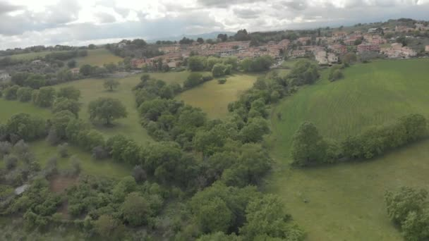 Oak forests and green meadows between hills with a spectacular sky and village skyline
