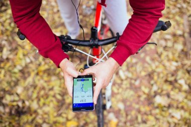 Autumn outdoors. Young handsome guy with earphones standing with bicycle in park and looking his cell phone with fitness navigation application. Photographed from above.