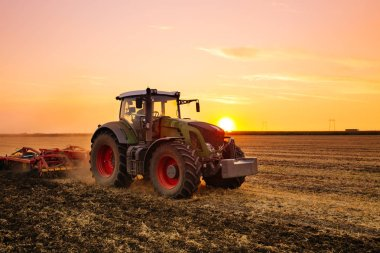 Tractor working on the barley field by sunset.