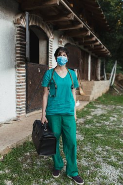 Veterinarian woman with protective mask standing and posing in front of horse stable and looking at camera