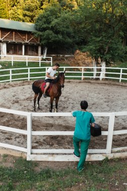 Veterinarian woman standing in front of horse coral and watching at injured and recovering animal with horseman