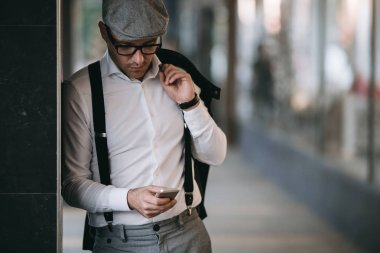 Fashionable retro dressed man wearing cap and eyeglasses on city street and using phone