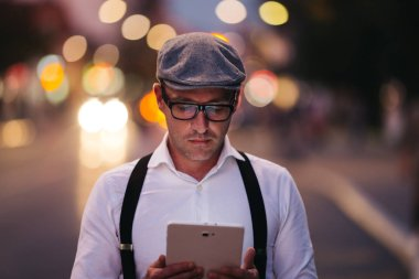 Fashionable retro dressed man with cap, suspenders and eyeglasses standing on city street and using tablet. City lights on sunset.
