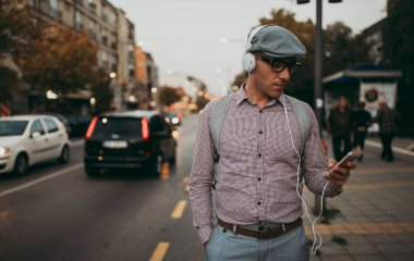 Fashionable retro dressed man with cap and eyeglasses standing on city street and using phone. City lights on sunset.