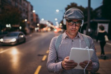 Fashionable retro dressed man with cap and eyeglasses standing on city street and using tablet. City lights on sunset.