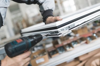 Manual worker assembling PVC doors and windows. Manufacturing job. Selective focus. Factory for aluminum and PVC windows and doors production.