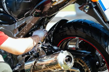 Adult and experienced biker cleaning and washing his motorcycle