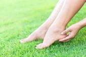 Nő kezében lábát a fájdalom a zöld fű természet háttér, az egészségügyi ellátás és az orvosi koncepció