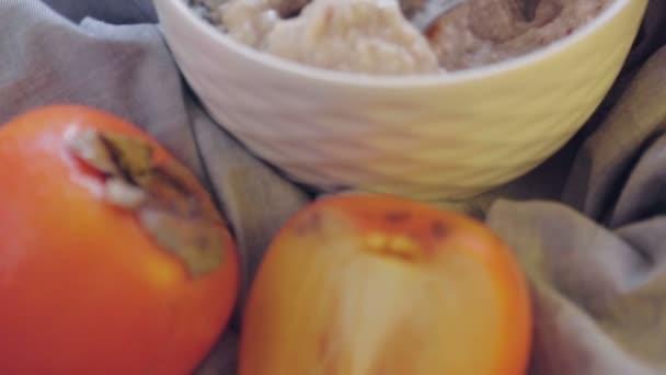 Ovesná kaše s persimmonem a švestkou v hluboké misce. Vařím zdravou snídani. Zdravé jídlo