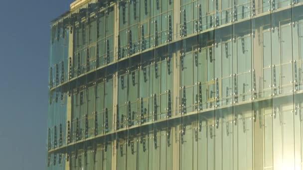 Krycí stěna ze skelné opony nakloněná nahoru. Spojovací prvky systému Spider Glass. Detaily fasády. Abstraktní pozadí architektury.
