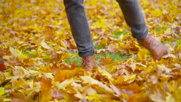 Muž v kožených botách se baví na spadlém listí. Zaparkujte na podzim. Outdoor city walk concept