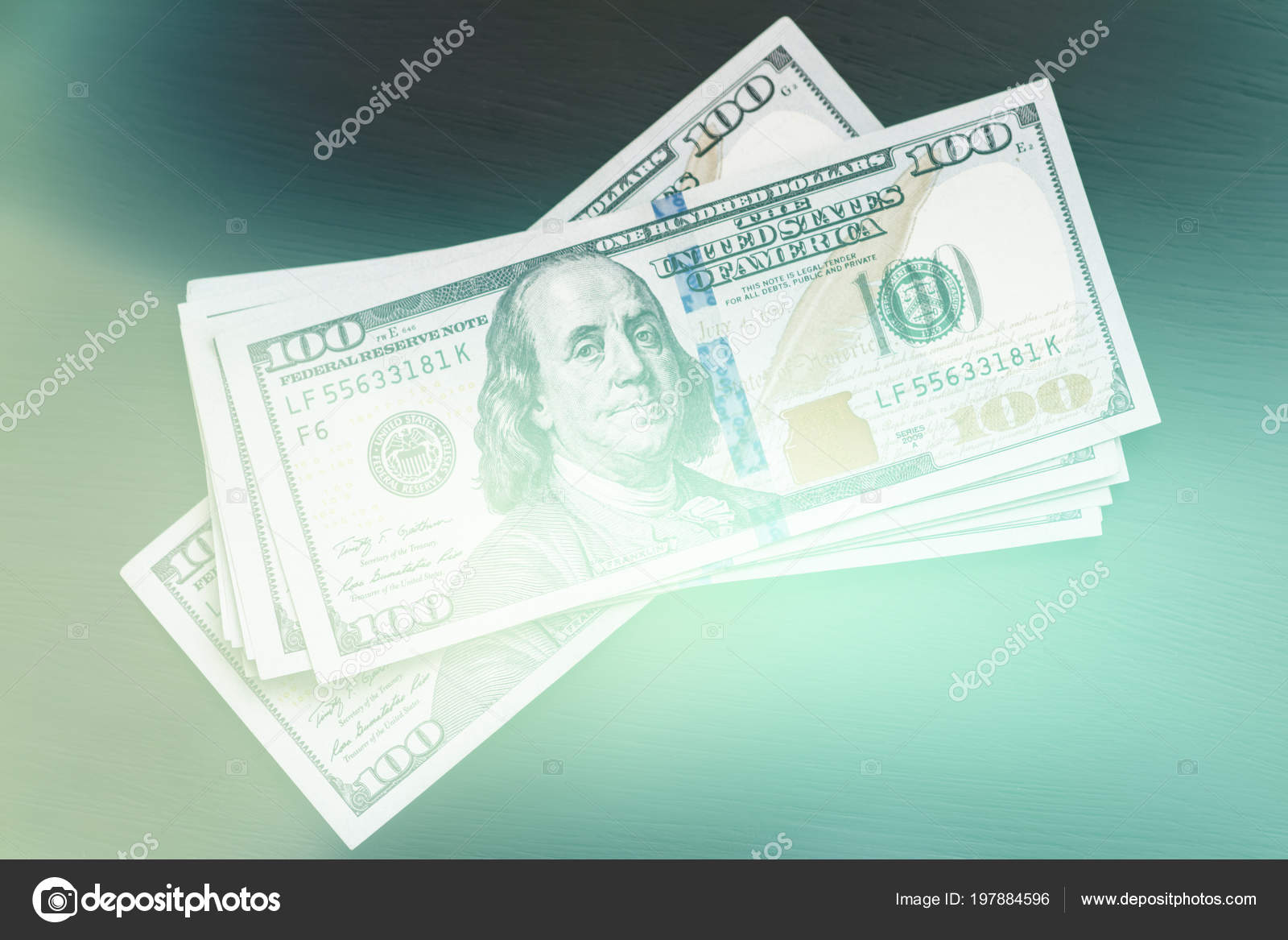 New US hundred-dollar bills on a black wooden textured table