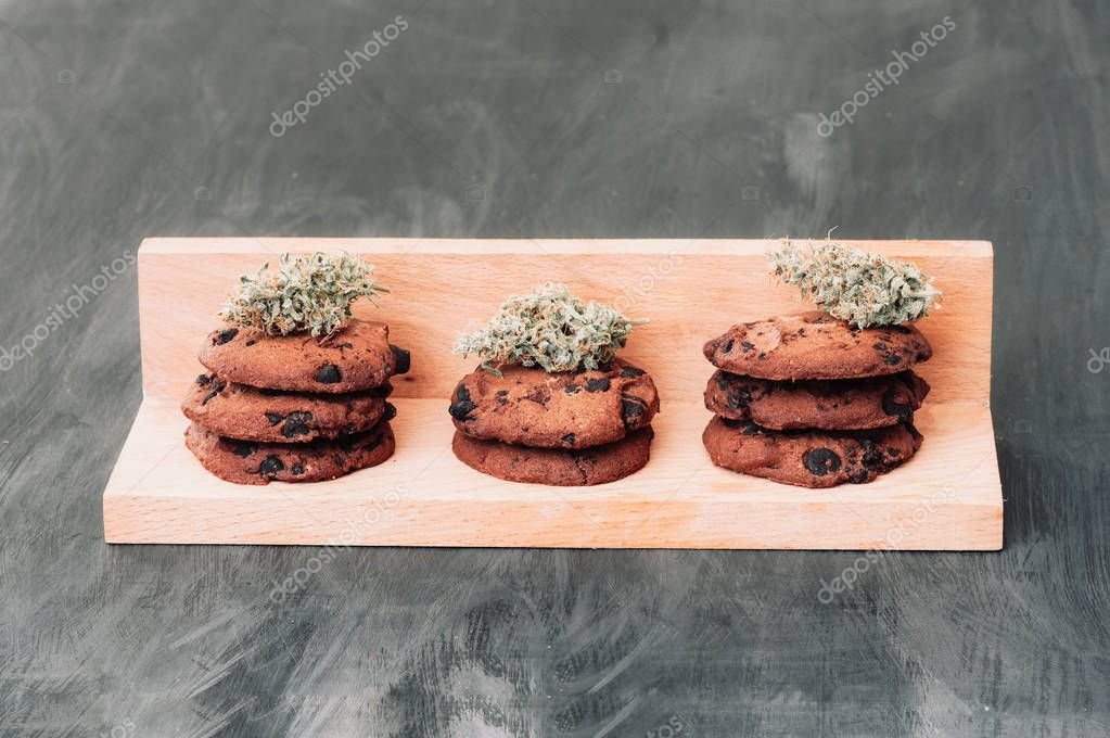 Sweets with cannabis. Cannabis buds on a black background. Baking with the addition of CBD. Sweets with weed. Chocolate cookies with marijuana. Copy-space