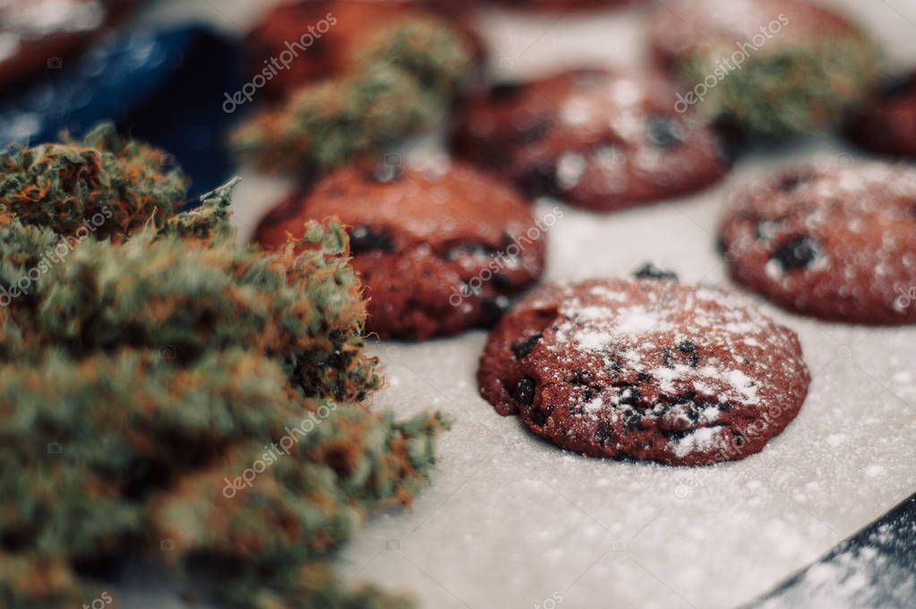 Chocolate cookies with marijuana. Sweets with cannabis. Cannabis buds on a black background. Baking with the addition of CBD. Sweets with weed.