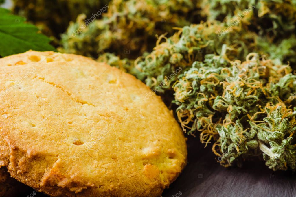 Sweets with weed. Cookies with marijuana. Sweets with cannabis. Cannabis buds on a black background. Baking with the addition of CBD.