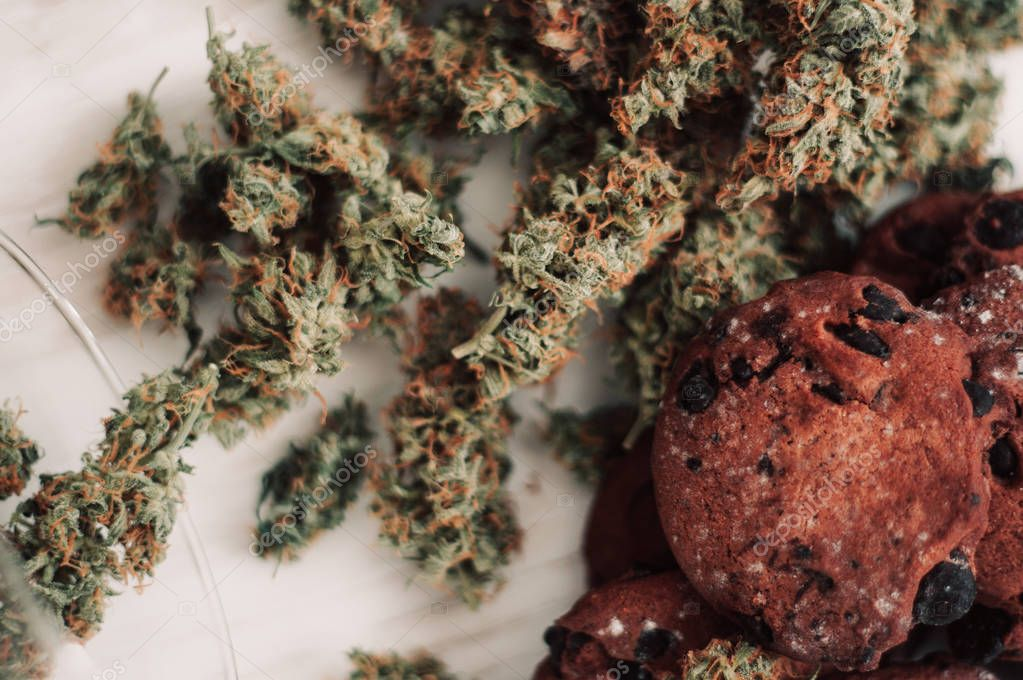 Cannabis buds on a black background. Baking with the addition of CBD. Sweets with weed. Chocolate cannabis.