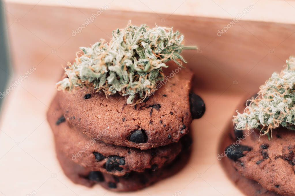 Cannabis buds on a black background. Baking with the addition of CBD. Sweets with weed. Chocolate cookies with marijuana. Sweets with cannabis.