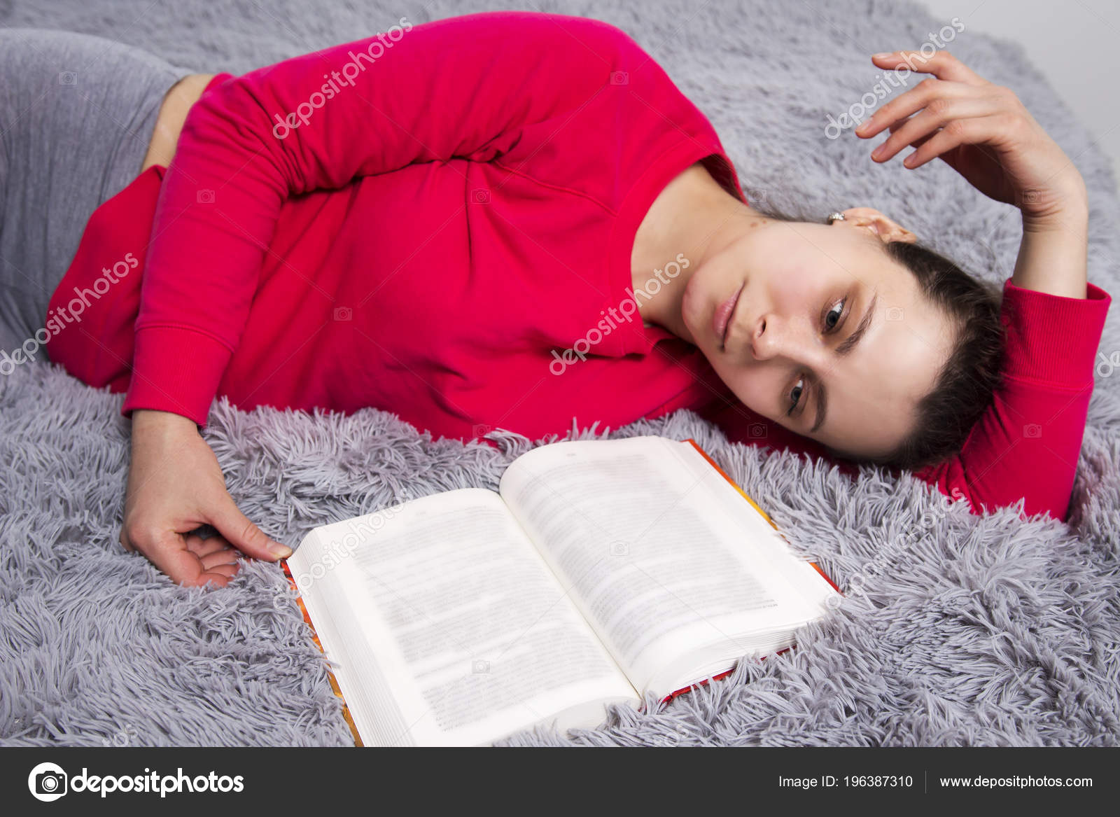 Girl is tired of reading book lying on bed  Attractive young
