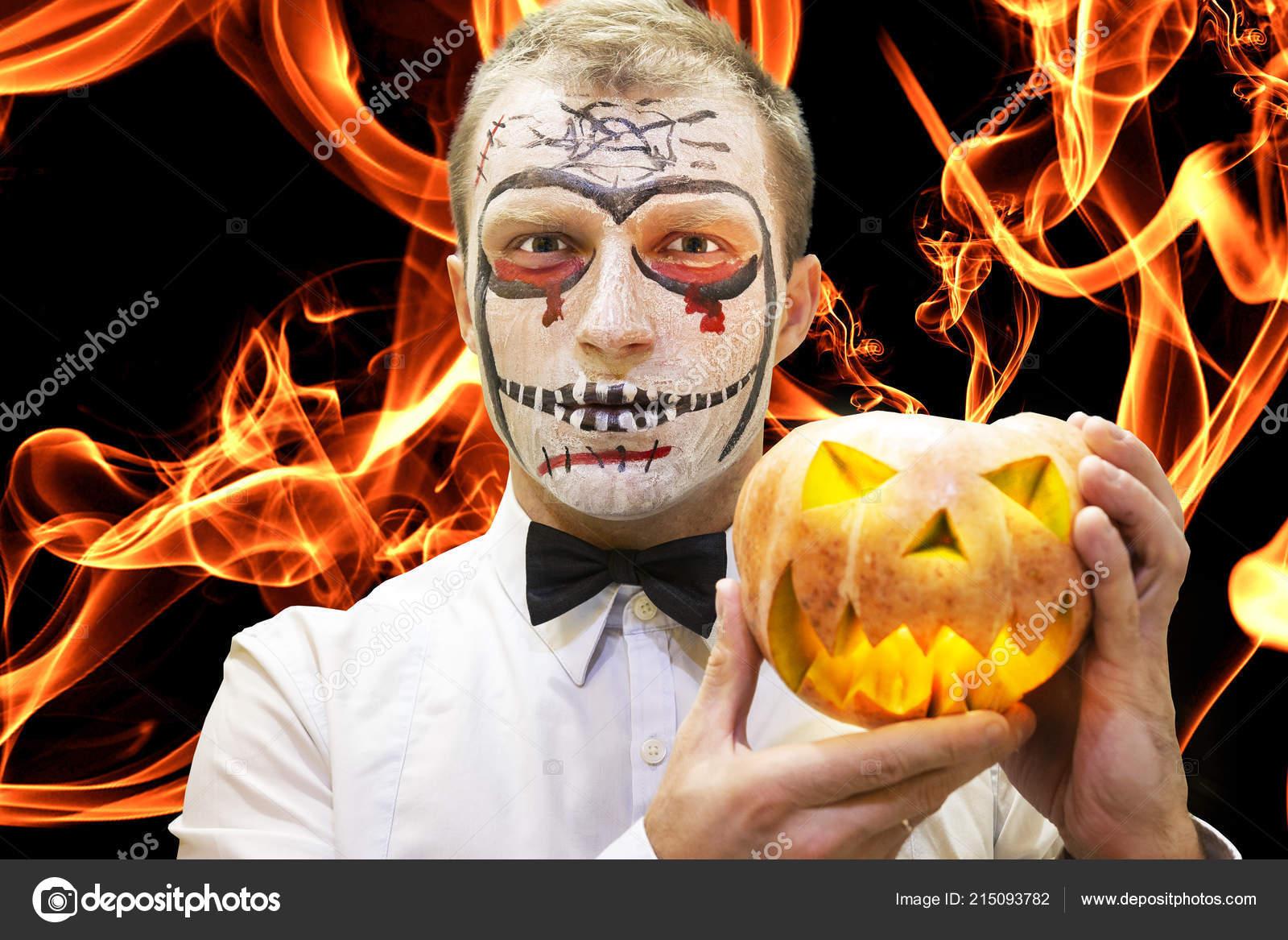 Halloween Make Up Men.Halloween Man With Pumpkin Against Burning Flame Of Fire