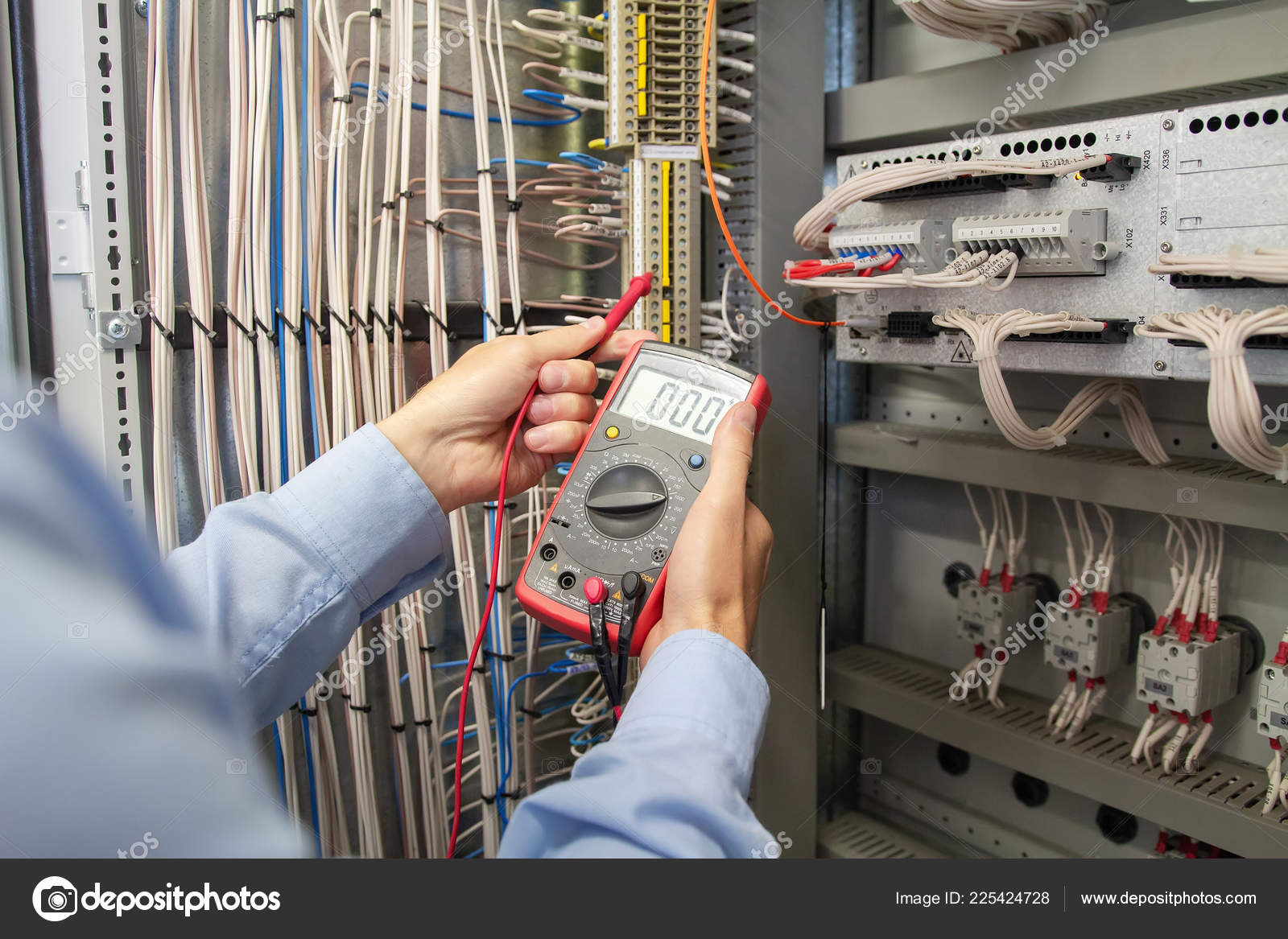 electrician engineer with multimeter in electrical cabinet stock