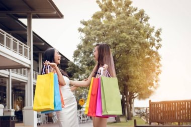 Funny two shopper asian woman holding paper bag and laugh togeth