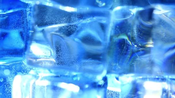 Nahaufnahme von Eiswürfeln aus Kristall, die in blau sprudelndem Brausewasser mit weißen Akzenten schwimmen