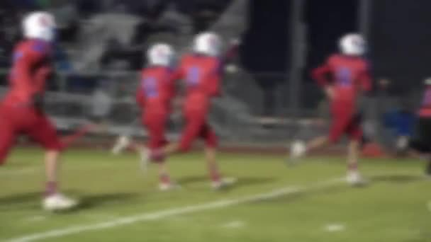 Defocused football players running into the locker room at half time