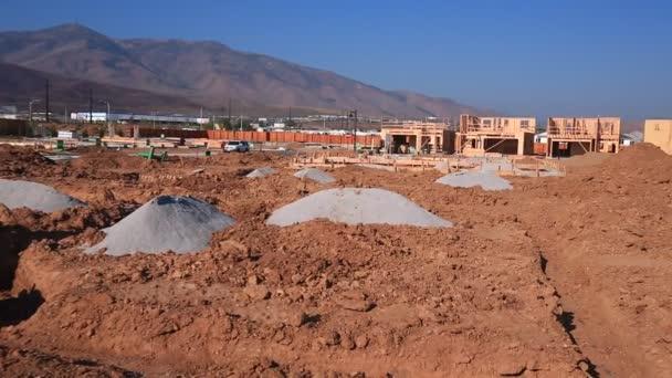 Přepálit vpravo nad prázdnými nečistými pozemky připravenými pro stavbu domu částečně postavené domy v pozadí